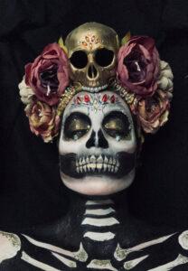 Halloween skull makeup on female model with headdress.