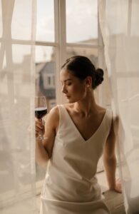A dark-haired bride in white dress sips wine from a glass whilst sitting in a window.