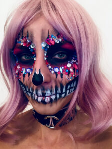 Woman with pink hair and skull makeup with gemstones for Halloween.