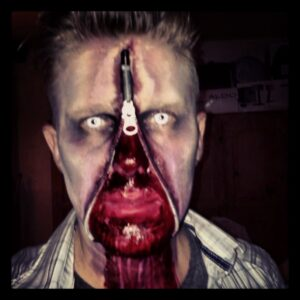 Halloween makeup showing a man with an unzipped, gory face.
