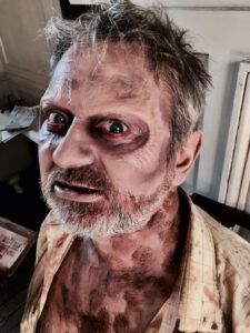 A man with zombie Halloween makeup, with prosthetics and body paint.