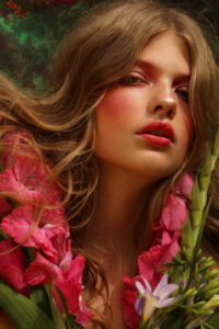 Fashion model with flowers and plants, with matching makeup.