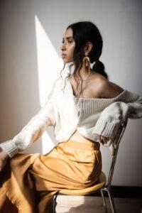 Fashion model with dark hair reclining in chair.